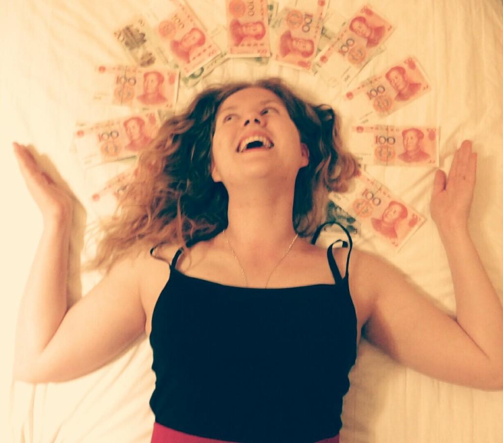 Aki liegt mit einer Krone aus chinesischen Geldscheinen im Bett